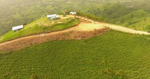 Aerial drone bird`s eye view video on a mountain covered with green grass. On top of the mountain there is a farm. Tropical paradise pacific atoll islands. Top stock video