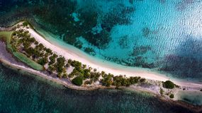 Aerial drone birds eye view of tropical island. Aerial drone birds eye view of tropical island with white sand and  turquoise clear waters Royalty Free Stock Photos