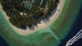 Aerial drone camera descending to the empty tropical white sand beach with an only couple lying in the sun on deck. Chairs on atoll island resort with palm stock footage