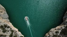 Aerial drone cinematic footage. Flying above speeding boat on the blue river in Lleida Congost del Mont-rebei stock footage