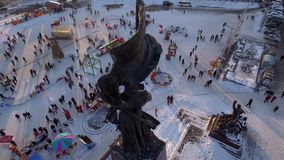 Central square monument close new year celebration decoration illumination carousel. Many people walk celebrate Winter Vladivostok. Aerial drone flight from stock footage