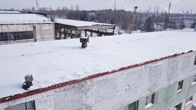 Aerial drone flight of the old metalworking plant in the snowy winter. Construction equipment and base. Aerial shot stock video footage