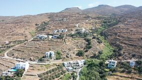 Aerial drone flight towards dry mountain landscape with few houses located on the hill in Tinos,Greece