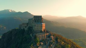 Aerial: drone flying at old medieval abbey perched on mountain top, stunning background of the snowy Alps at sunrise. Sacra di San. Michele italian - Saint stock video