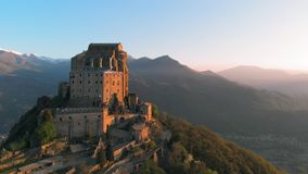 Aerial: drone flying at old medieval abbey perched on mountain top, stunning background of the snowy Alps at sunrise. Sacra di San. Michele italian - Saint stock footage