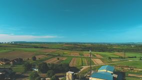 Aerial drone is flying over farm lands and houses. 4K. Slowly flying over the countryside area. Copy space stock video