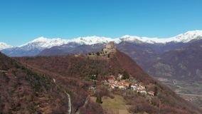 Aerial: drone flying over forest reveals snow capped mountains and Sacra di San Michele Saint Michel Abbey on top, Turin, Italy stock video footage