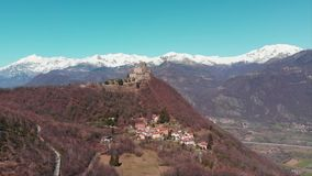 Aerial: drone flying over forest reveals snow capped mountains and Sacra di San Michele Saint Michel Abbey on top, Turin, Italy stock footage