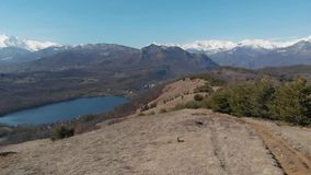 Aerial: drone flying over forest valley lake, aerial view of snow capped mountain range on the Alps, clear blue sky. Turin, Italy stock footage