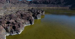 Aerial drone flyover of reflecting volcanic lake 4k 24fps. Fly aerial drone flyover of reflecting volcanic lake stock footage