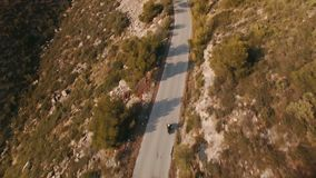 Drone footage over lonely traveler riding his motorbike on epic scenery mountain roads