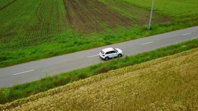 Aerial drone footage of a car travelling along a country road.  stock video footage