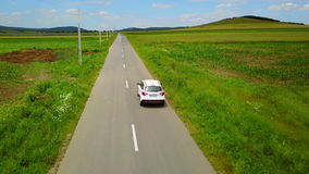 Aerial drone footage of a car travelling along a country road.  stock footage