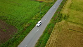 Aerial drone footage of a car travelling along a country road.  stock video
