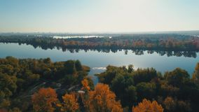 Aerial drone footage. Flight over autumn forest to river