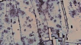 Aerial drone footage flying low over the while houses and streets are covered in snow. Aerial drone footage flying low over in the while houses and streets are stock video footage