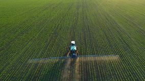 4K aerial drone footage. Following tractor sprayer on soybean fields