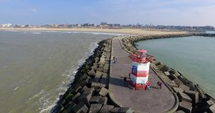 Aerial drone footage of pier with lighthouse and coastline in Holland stock video footage