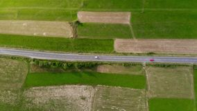 Aerial drone footage, two cars driving on the road between the fields