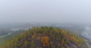 Aerial Drone Footage. View of autumn hills with forests, meadows and hills in fog at sunset, very soft light. Fog over the city. Small hills in Europe. Majestic stock footage