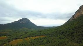 Aerial Drone Footage View: Flight between cloudy mountains Pic Saint Loup
