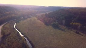 Aerial Drone Footage View: Flight over autumn mountains and small river with forests in sunrise soft light.