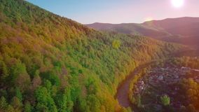 Aerial Drone Footage View: Flight over spring mountain village with forest in sunrise soft light. Image processed in. Orange glow. Carpathian Mountains, Ukraine stock footage