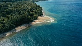 Aerial drone image of a remote south pacific island with sandy beach shore and beautiful ocean sea seascape and lush tropical royalty free stock images