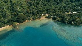 Aerial drone image of a south pacific village on a remote island with a beautiful coral reef and lush tropical rainforest jungle. While a small motor boat royalty free stock image
