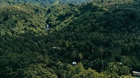 Aerial drone image of a south pacific village on a remote island with sandy beach shore and lush tropical rainforest jungle with stock photo