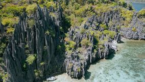 Aerial drone movement along sharp cliffs of unique island El Nido, Palawan, Philippines. Bizarre limestone rocks and. Lonely and steep coast. Tour C stock video