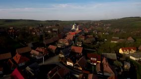 Aerial drone moving above village and church tower. Transylvania, Romania stock video footage