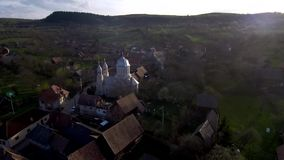 Aerial drone moving above village and church tower. Transylvania, Romania stock video