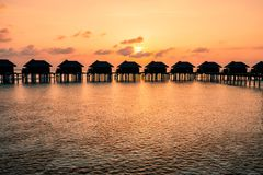 Aerial drone photo - Above water bungalows in the Maldives at sunrise. royalty free stock photo