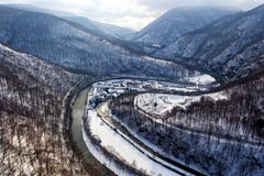 Aerial drone view of a mountain valley during winter. Aerial drone photo of a beautiful monastery in Romania set in a charming winter landscape with snow Royalty Free Stock Photos