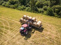 Aerial Drone Photo of Farmer Harvesting Hay Rolls in the Wheat F. Ield with a Red Tractor - Sunny Summer Day royalty free stock photo