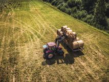 Aerial Drone Photo of Farmer Harvesting Hay Rolls in the Wheat Field with a Red Tractor - Sunny Summer Day, Vintage Look Edit.  royalty free stock photos