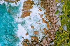 Aerial drone photo of Seychelles tropical beach Anse Cocos at La Digue Island. White rolling waves splash granite. Coastal rocks. Travel and vacation concept stock photos
