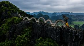 Aerial drone photo - Woman next to a dragon shrine atop a mountain in northern Vietnam.  Hang Mua stock images