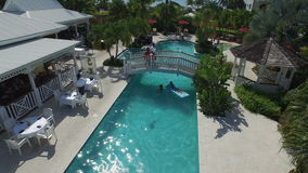 Aerial drone of resort pool with a bridge. Aerial drone flying up from a resort pool with crystal clear turquoise water and a bridge in between stock footage