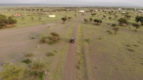 Aerial Drone Shot. Black Car is moving Through the Traditional Masai village at Sunset time near Mto wa Mbu, Arusha