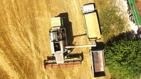 Aerial drone shot of a combine harvester loading a truck in a field. At sunset. Shot in 4K (UHD stock video footage