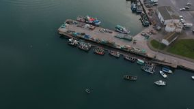 Aerial drone shot of fishing boats in fishing harbor in Portugal, with fishing nets drying in the sun on jetty. Aerial drone shot of small fishing boats berthed stock footage