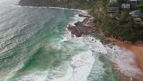 Aerial drone shot of an ocean rock pool near Sydney, Australia. Aerial drone shot of an ocean rock pool on the beach with swimmers near Sydney, NSW, Australia stock footage