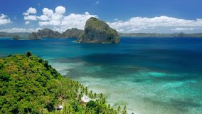 Aerial drone shot of remote coastline of Bacuit bay. Green jungle, turquoise ocean, tropical islands. El Nido, Palawan. Philippines. Summer and travel vacation stock video footage