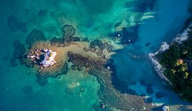 Aerial drone shot of a rock and beautiful turquoise waters at Corfu Greece. royalty free stock image