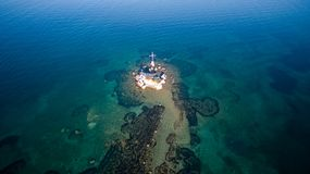 Aerial drone shot of a rock and beautiful turquoise waters at Corfu Greece.  Royalty Free Stock Photos