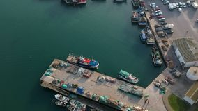Aerial drone shot of fishing boats berthed in harbour in Portugal, with fishing nets drying in the sun on jetty. Aerial drone shot of small fishing boats berthed stock video footage