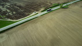 Aerial drone shot to the countryside roadway. Truck with product driving through the empty motorway. Beautiful countryside landscape of the field after stock video footage