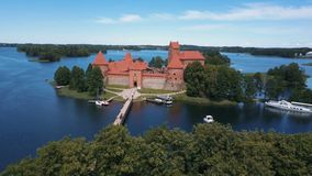 Aerial drone shot of Trakai castle in Lithuania. Flight over trees. Beautiful castle on the lakes. Aerial view of Trakai. Trakai castle, Lithuania. Beautiful stock video
